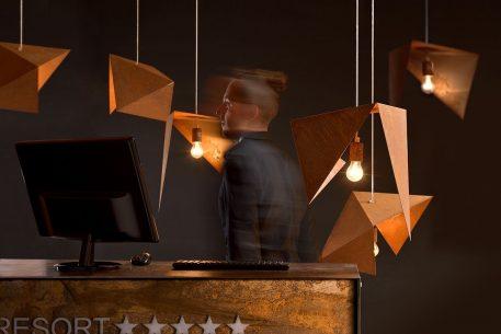 Lampy origami pokryte rdzą w aranżacji biurowej